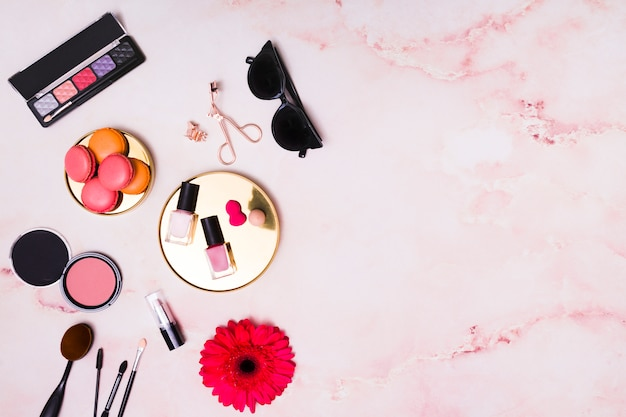 Macaroons; sunglasses and cosmetics products on pink textured background Free Photo