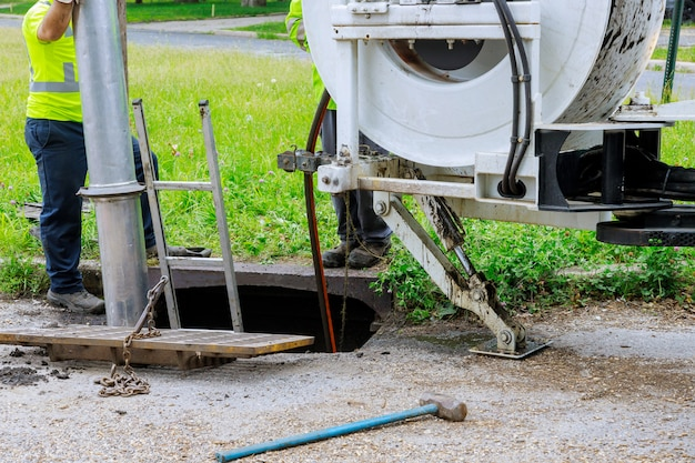 Machine for cleaning sewer wells in the a town street. Premium Photo