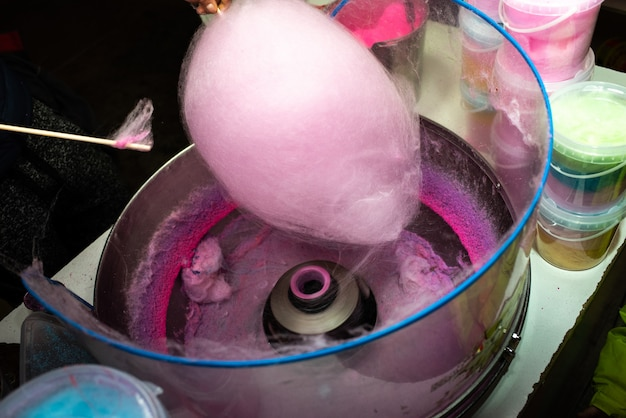 Machine to make cotton candy by turning and toasting the pink sugar Premium Photo