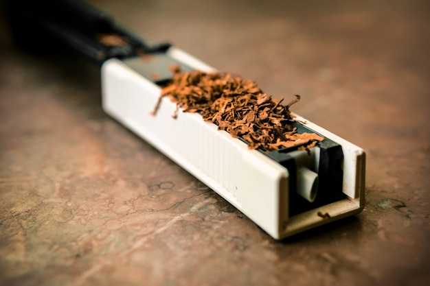 The machine for stuffing cigarettes with tobacco. empty sighety. rossypany tobacco on the table. homemade cigarette production Premium Photo