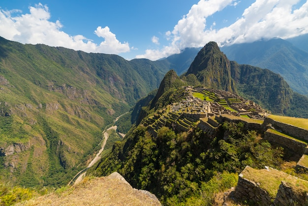 Machu picchu illuminated by the sunlight. wide angle view from the terraces above with scenic sky. Premium Photo