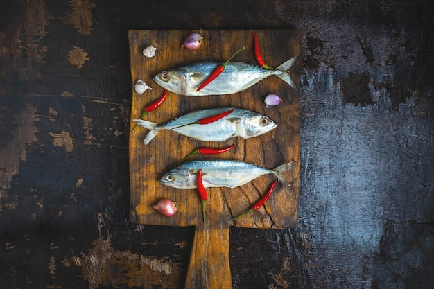 Mackerel fish on wooden chopping board Premium Photo