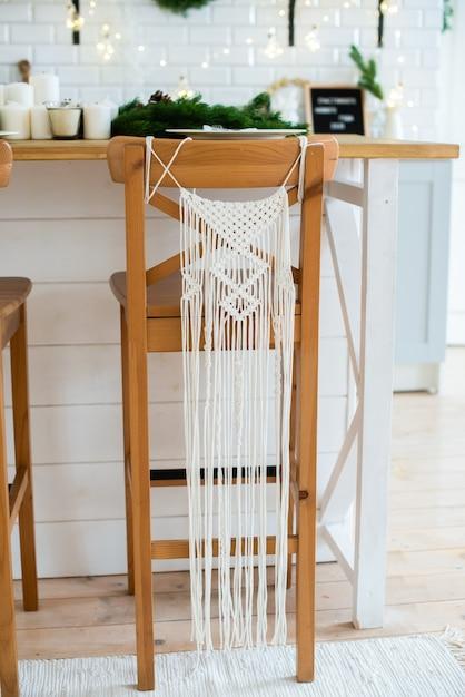 マクラメ。 diy。リビングルームの装飾。木製の椅子にマクラメ。居心地の良い素朴なスタイル。 Premium写真