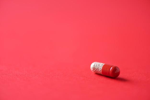 Макрос красных капсул на красной предпосылке. копировать пространство куча лекарств, лечение простуды. Premium Фотографии