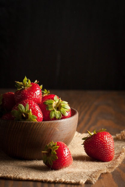 Macro photo of fresh ripe red strawberry in a wooden bowl on rustic background. organic natural products. Premium Photo