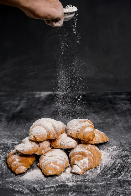 灰色のテーブルに粉砂糖をクロワッサンのマクロ写真。 無料写真