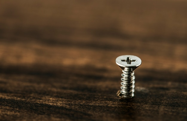 Macro shot of screw on wooden background Free Photo