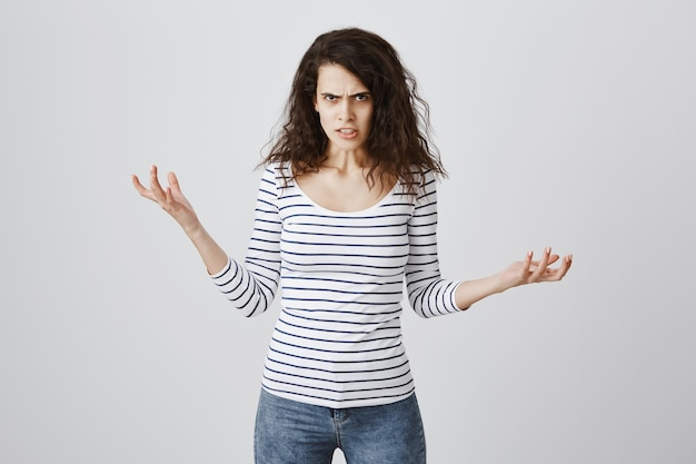 Сумасшедшая и раздраженная женщина жалуется, пожимает руки и хмурится Бесплатные Фотографии
