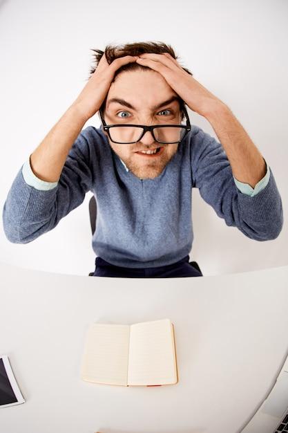 Безумный и расстроенный молодой человек, находящийся под давлением, расчесывающий волосы и морщась, сердитый как работа, сидящий стол не может придумать идеи Бесплатные Фотографии