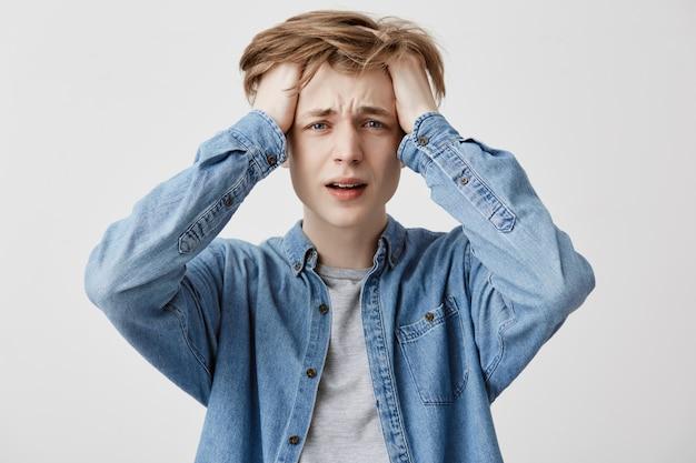 Il pazzo pazzo che si rammarica per gli errori, vestito con una camicia di jeans, capisce che non può cambiare nulla o tornare indietro per migliorare la situazione, essere nel panico e nello stress. grande disperazione Foto Gratuite