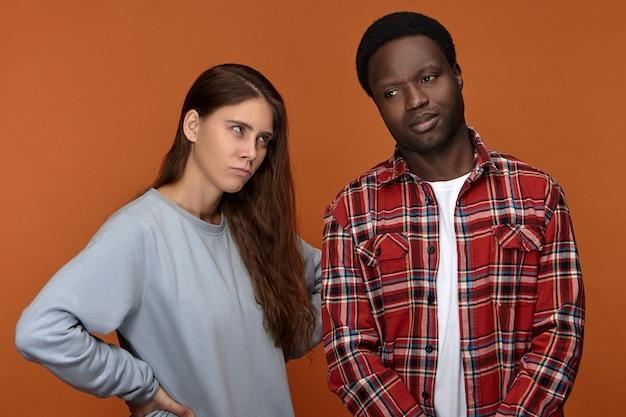 Mad dispiaciuta giovane donna con i capelli lunghi che guarda con rabbia il suo ragazzo afroamericano nero arrabbiato che si è dimenticato del suo compleanno. coppia interrazziale che ha problemi e difficoltà di relazioni Foto Gratuite