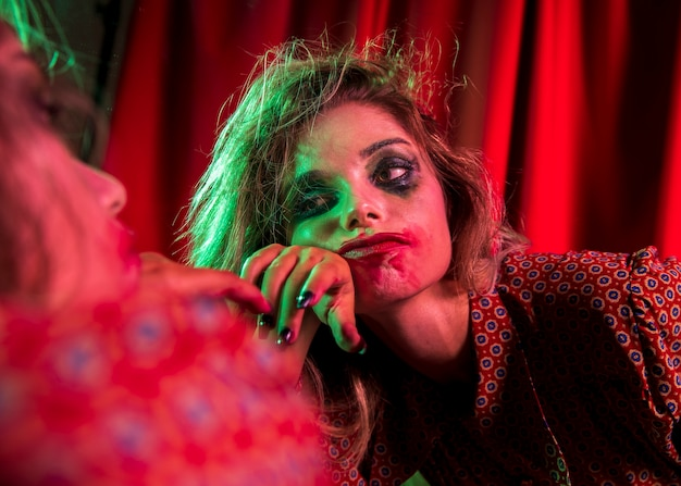 Mad halloween clown woman being bored Free Photo
