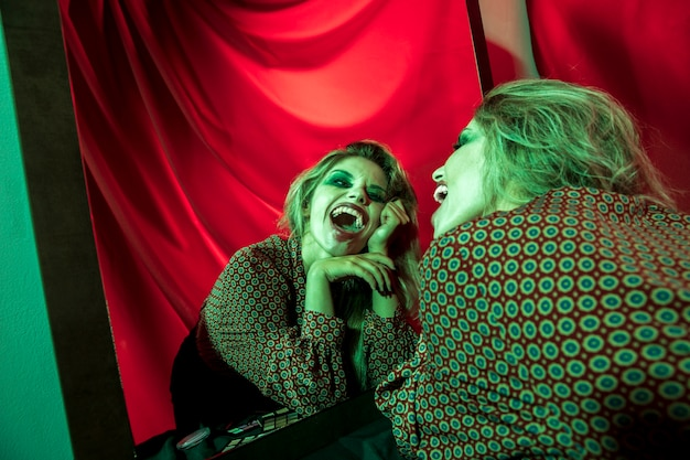 Mad halloween clown woman laughing at the mirror Free Photo