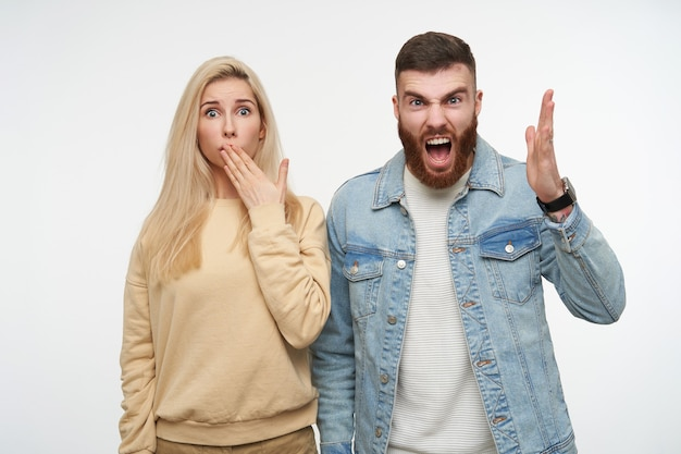 Mad young pretty brunette guy with beard raising emotionally his hand while screaming angrily, posing on white with bewildered blue-eyed blonde lady coning her mouth Free Photo
