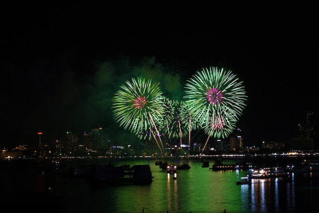 Magenta green fireworks on beach and reflection color on water surface Premium Photo
