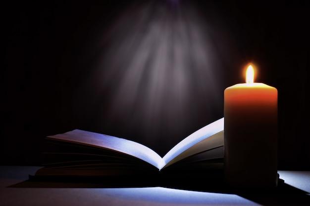 마법의 책과 촛불. 성경 책과 신비한 빛. 프리미엄 사진