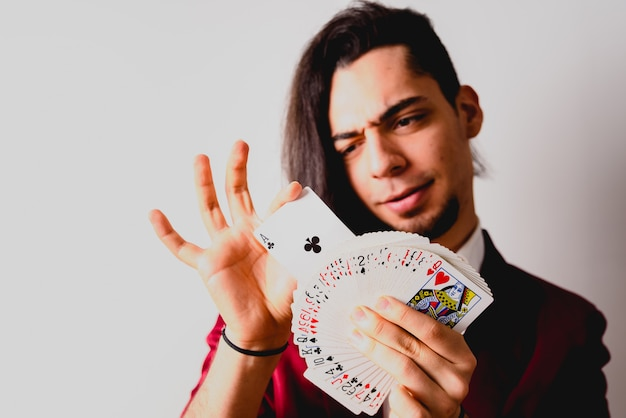 Magician doing tricks with a deck of cards. Premium Photo