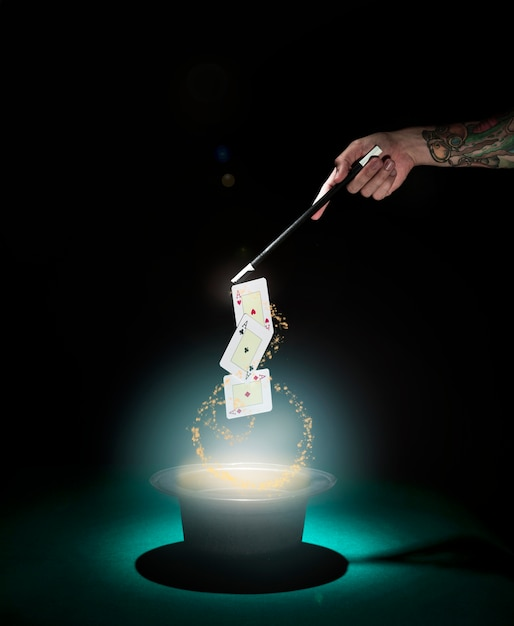 Magician performing playing card trick over the top hat with glowing lights against black background Free Photo