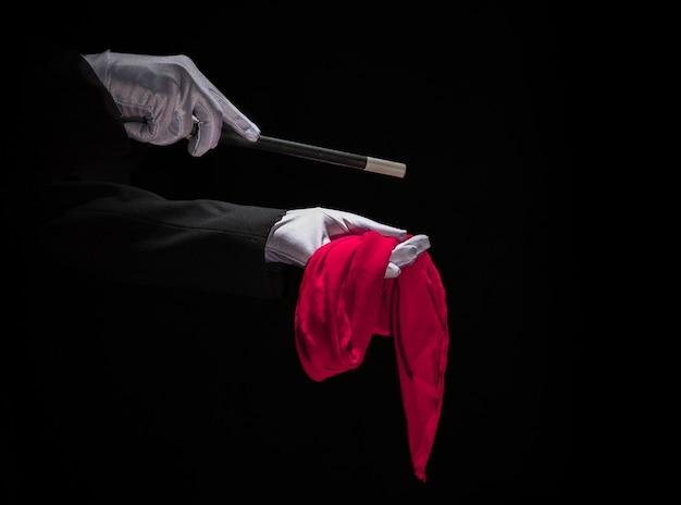 Маг, выполняющий трюк на красной салфетке с волшебной палочкой на черном фоне Premium Фотографии