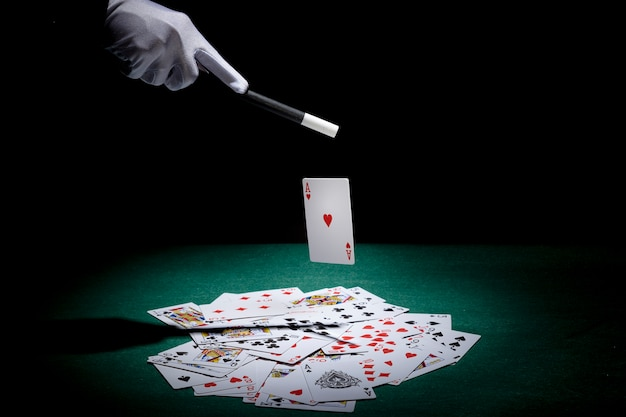 Magician performing trick on playing cards with magic wand on poker table Free Photo