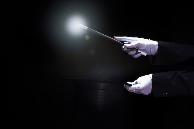 Magician performing trick with magic wand over the black top hat against black background Free Photo