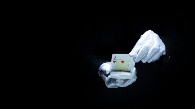 Magician performing trick with playing cards against black background Free Photo