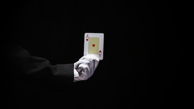 Magician's hand holding aces playing card against black background Free Photo