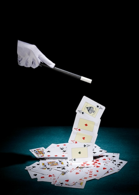 Magician's hand picking up aces cards with magic wand over poker table Free Photo