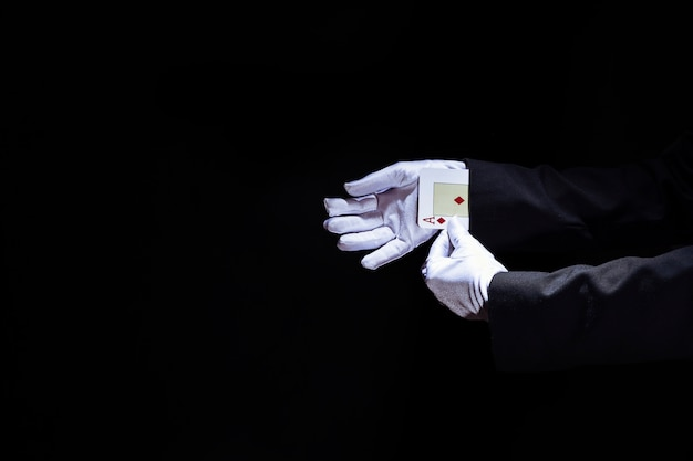 Magician's hand removing aces playing card from the sleeve against black background Free Photo