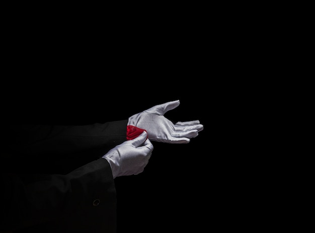 Magician's hand removing red napkin from the sleeve against black background Free Photo