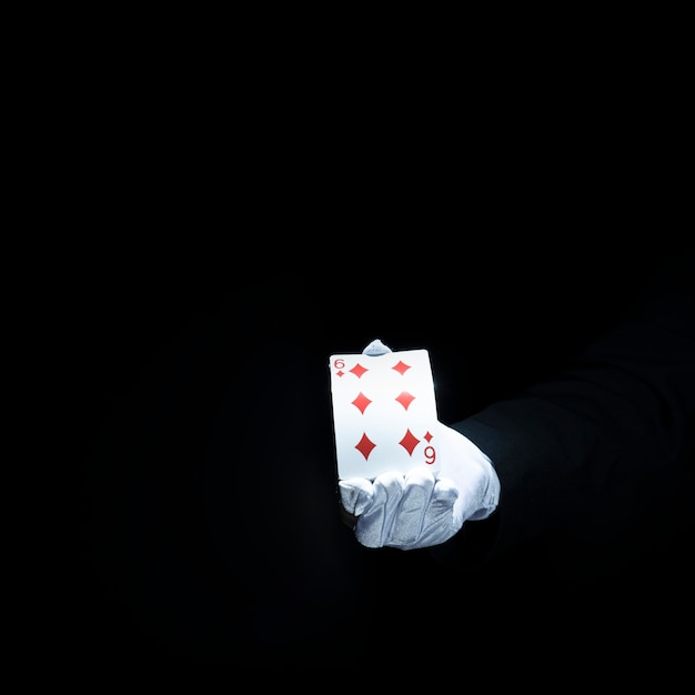 Magician's hand showing diamond playing card against black background Free Photo
