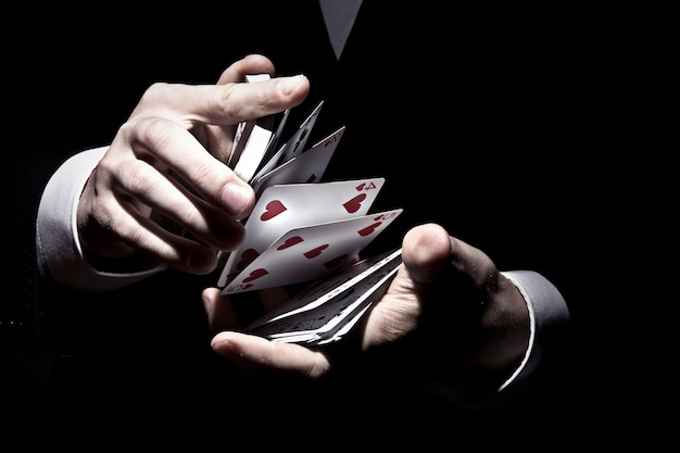 Magician shuffling the cards in a cool way under the spotlight Free Photo
