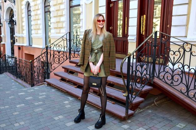 Великолепная блондинка, стильная женщина позирует на берегу реки возле роскошного отеля в классическом стиле, европейская атмосфера, современный модный наряд, блогер позирует на улице. Бесплатные Фотографии