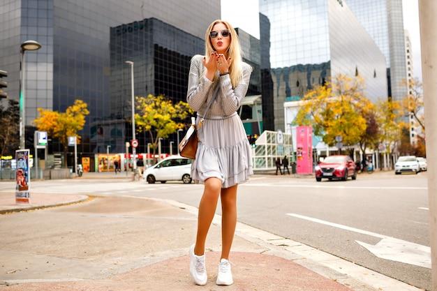 Великолепная довольно элегантная блондинка в женственном модном платье и свитере, посылающая воздушные поцелуи, в полный рост, осень-весна в середине сезона, турист в нью-йорке. Бесплатные Фотографии