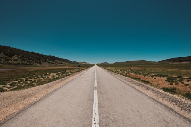 Magnificent view of an endless road under the clear blue sky Free Photo