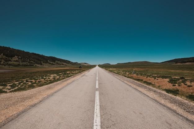 Magnifica vista di una strada infinita sotto il cielo blu chiaro Foto Gratuite