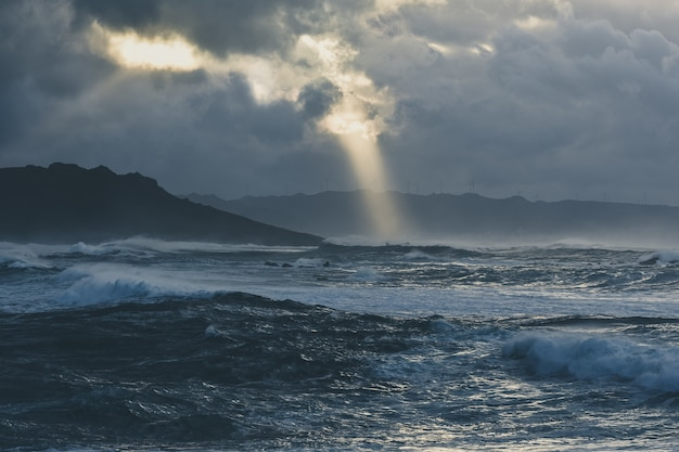 曇りの夜に捉えられた嵐の海の壮大な波 無料写真