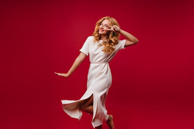 Великолепная женщина в белом платье, выражающем счастье. прелестная блондинка танцует на красной стене. Бесплатные Фотографии