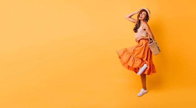 Magnificent woman in long bright skirt dancing in studio. carefree inspired female model posing with pleasure on yellow. Free Photo