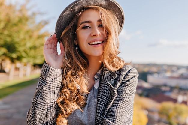 Magnifica giovane donna con bellissimi occhi azzurri in posa in cappello su sfocatura dello sfondo della città Foto Gratuite