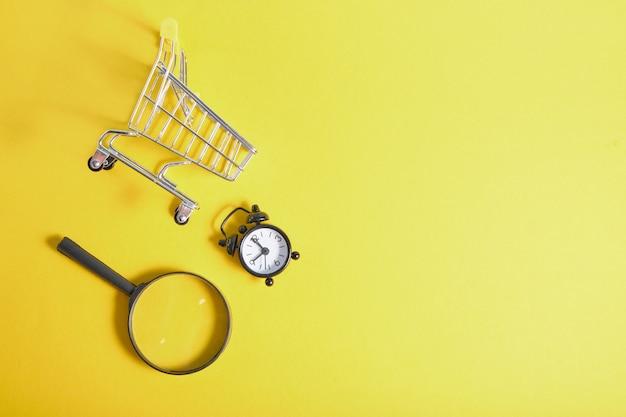 노란색 배경 상위 뷰 복사 공간에 돋보기, 알람 시계 및 소형 쇼핑 바구니 프리미엄 사진