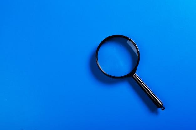 Magnifier on blue background close up Premium Photo