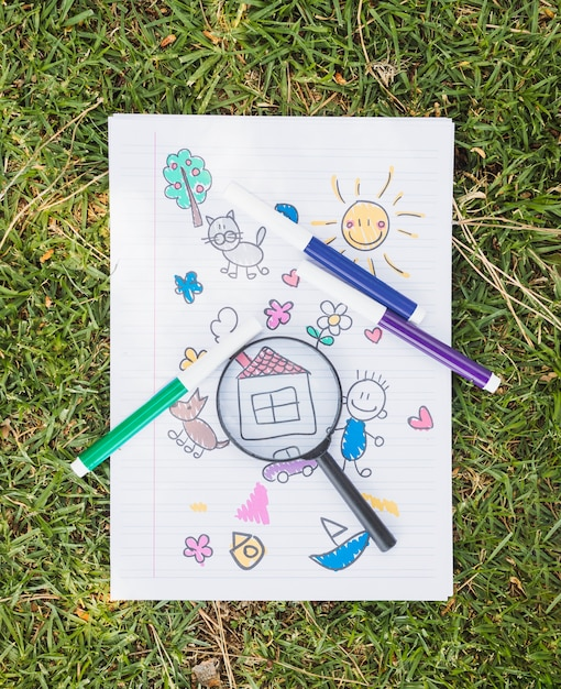 Magnifier on childish drawing on grass Free Photo