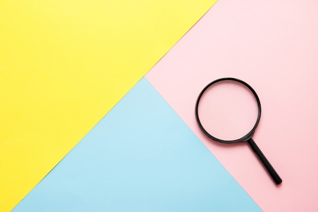 Magnifier on colored paper. top view. search concept Premium Photo