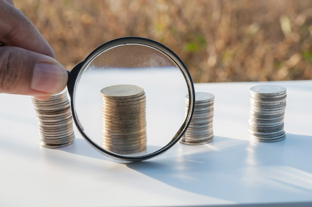 Magnifier searching investment of stacking coin growing Premium Photo