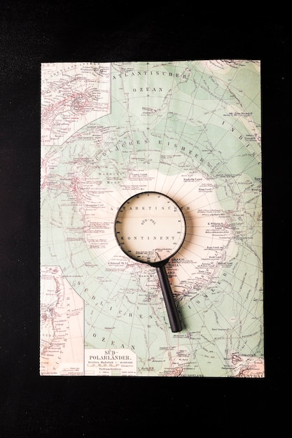 Magnifying glass on atlas Free Photo