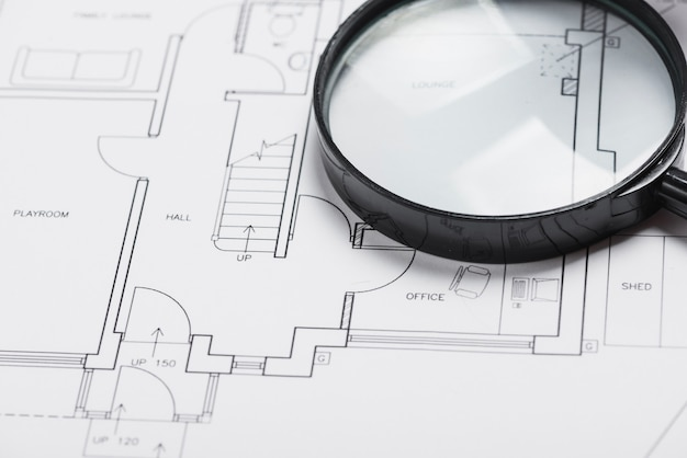 Magnifying glass on blueprint Free Photo