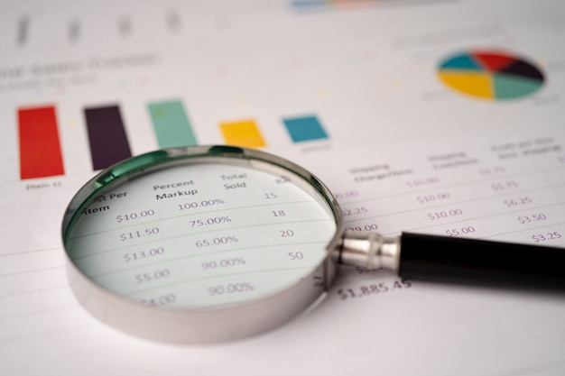 Magnifying glass on charts graphs paper. Premium Photo