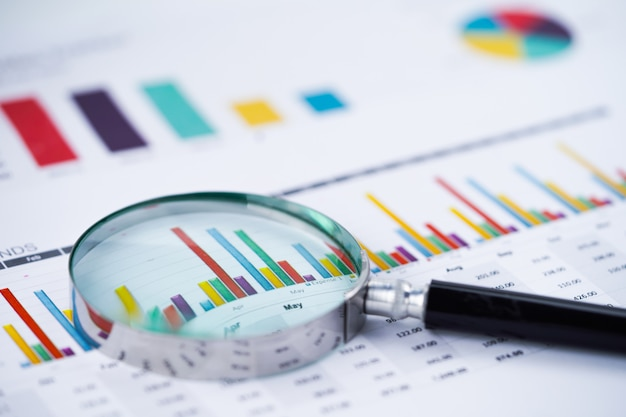 Magnifying glass on charts graphs spreadsheet paper. Premium Photo