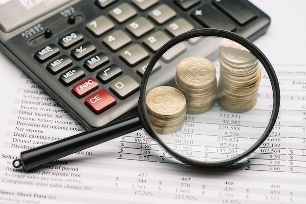 Magnifying glass over the coin stack and calculator on financial report Free Photo